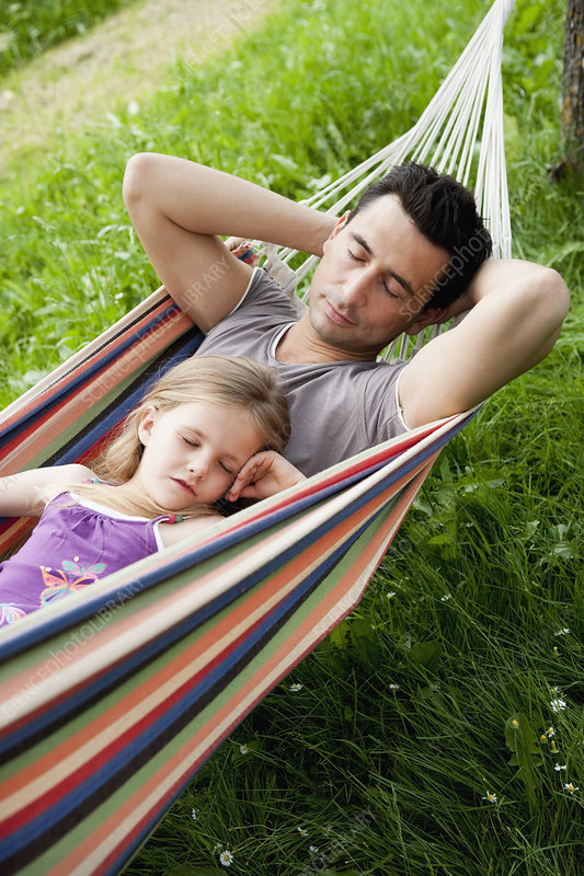 Father And Daughter Sleeping In Hammock