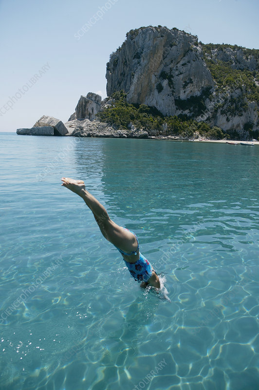 Woman diving into blue water from boat