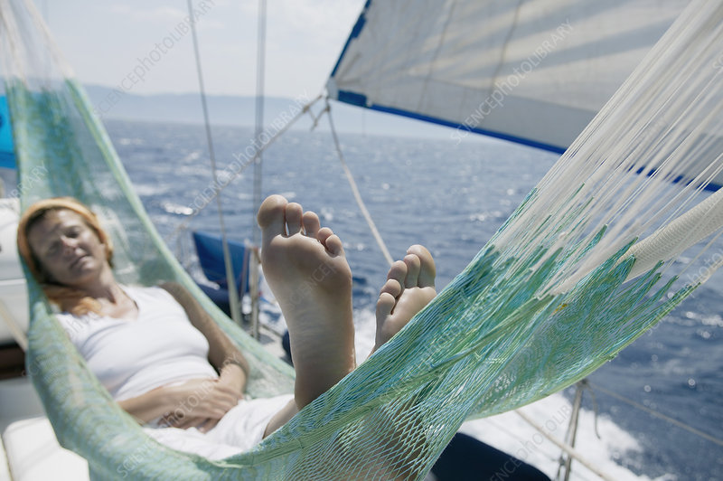 Woman lying in hammock on sailing boat