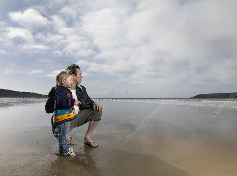man and child looking out to sea on beach