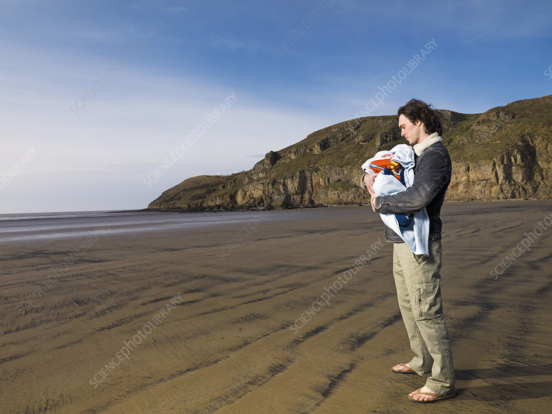 man on beach holding baby