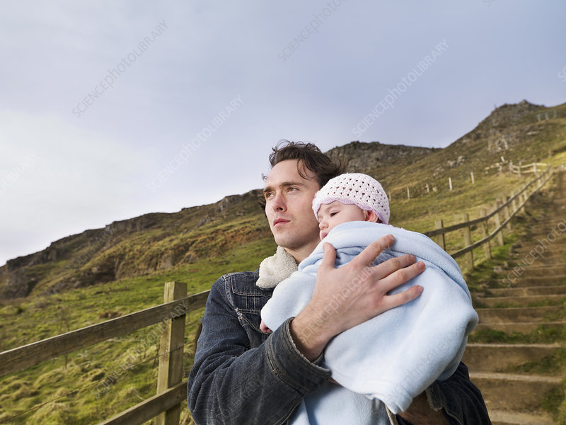 man on hill path holding baby
