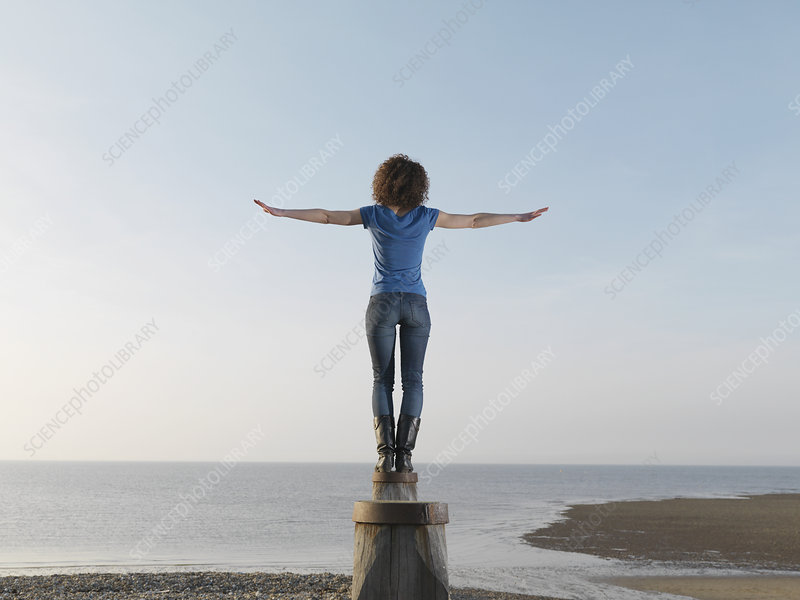 Woman balancing on wooden post