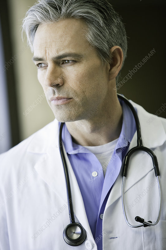 Male Doctor looking out window thinking