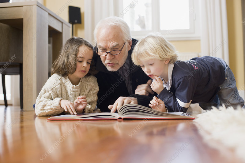 old man reading book to children