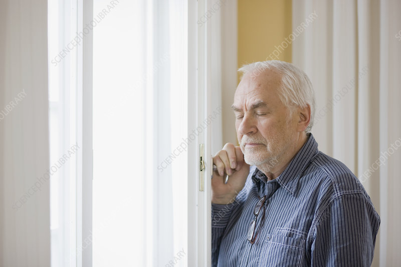 old man standing at window