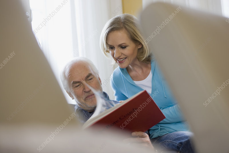 old father and daughter reading book