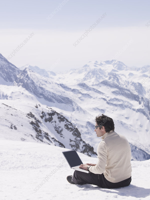 man sitting in the snow using laptop