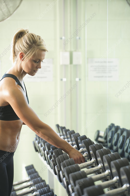 Woman picking up barbell in gym