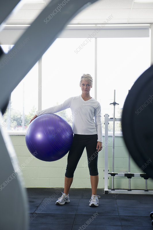 Woman holding exercise ball in gym