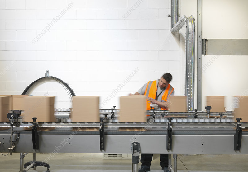 Factory worker checking boxes in plant