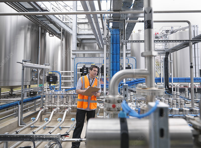 Worker with machinery in bottling plant