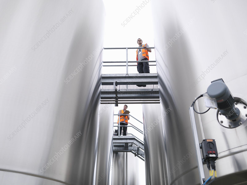 Workers checking tanks in bottling plant