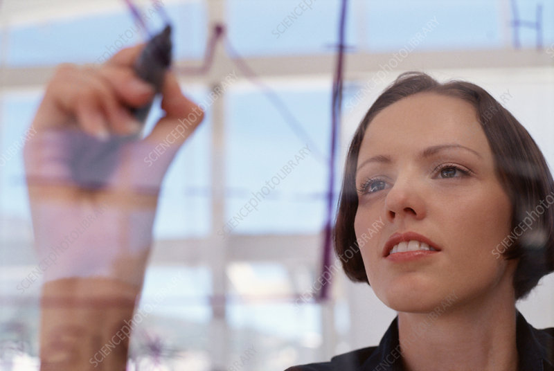Businesswoman drawing graph on glass