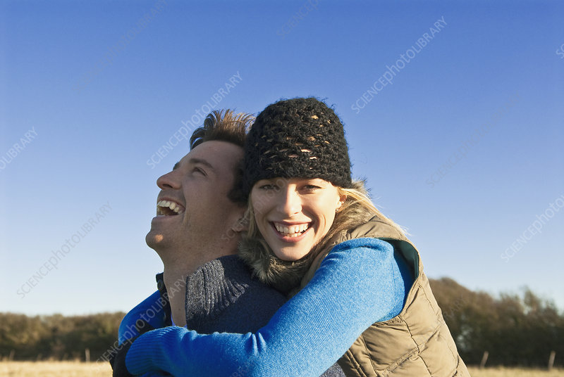 Smiling couple hugging in field