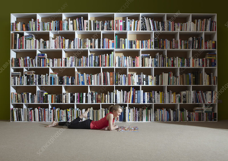 Girl reading by bookshelves