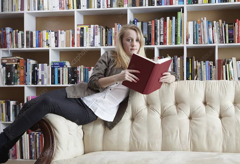 Girl reading on couch in library
