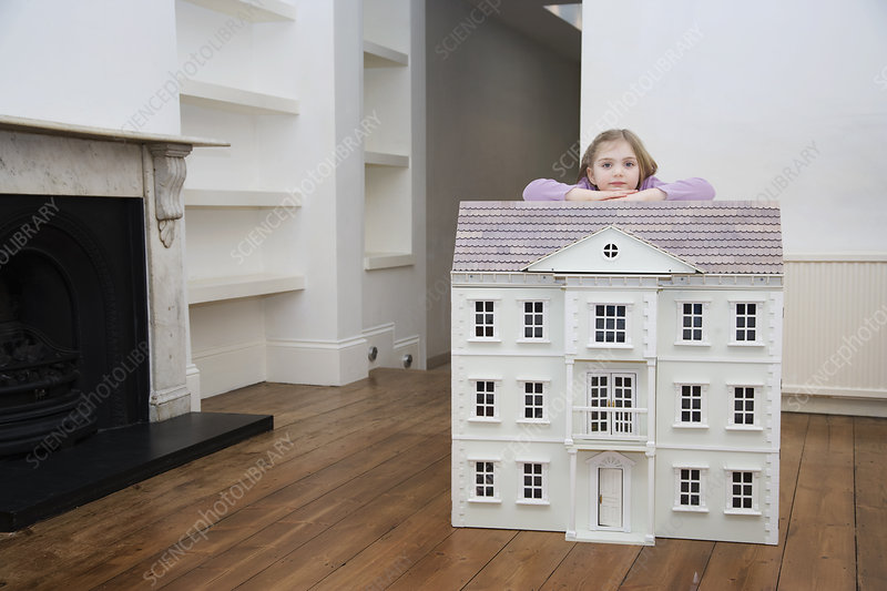 A girl resting on her dollhouse