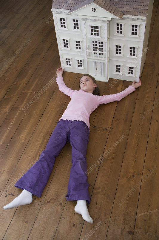A girl lying in front of her dollhouse