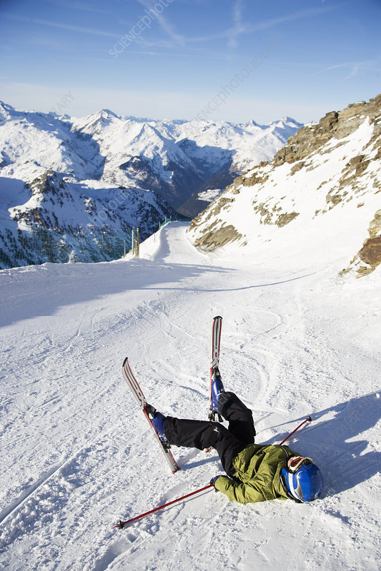 Child on skis lying in the snow