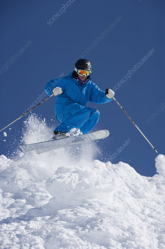 Man in blue jump-suit skiing
