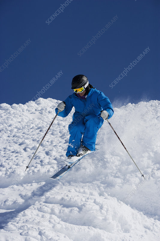 Man in blue skiing down hill