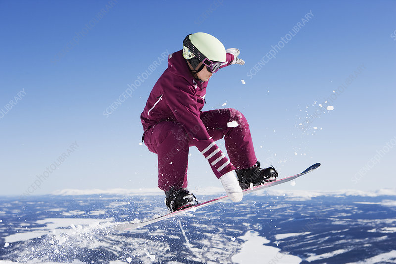 Girl in jumpsuit grabbing board mid-air