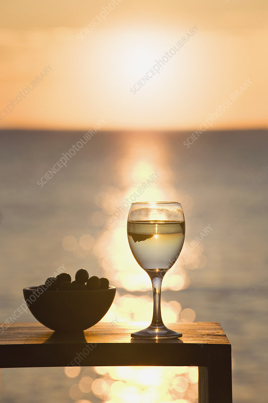 A glass of wine and olives at sunset