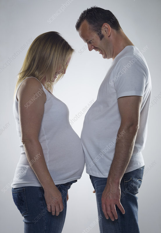 pregnant woman comparing bump with man