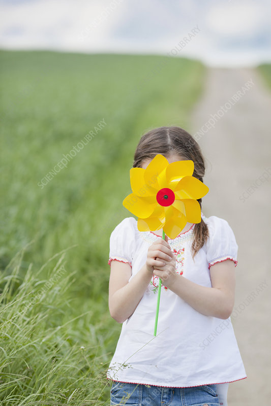 young girl playing with toy windmill