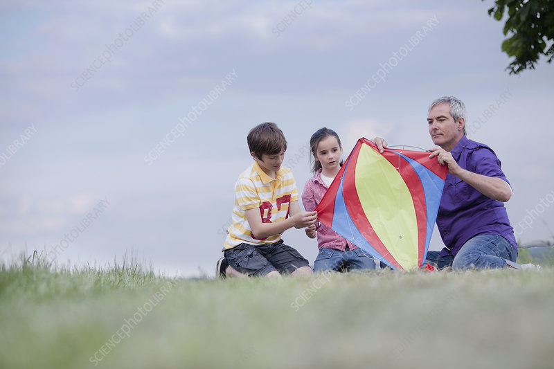 family of three building kite