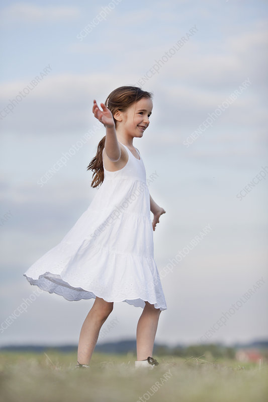 young girl dancing in the grass