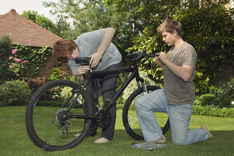 Boys fixing bicycle together