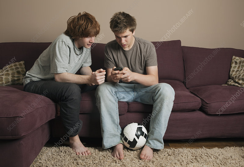 Boys sending message from mobile phone