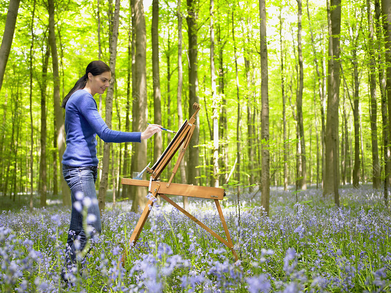 Woman painting in the forest