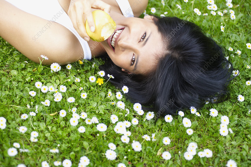 Woman eating an apple in the daisies