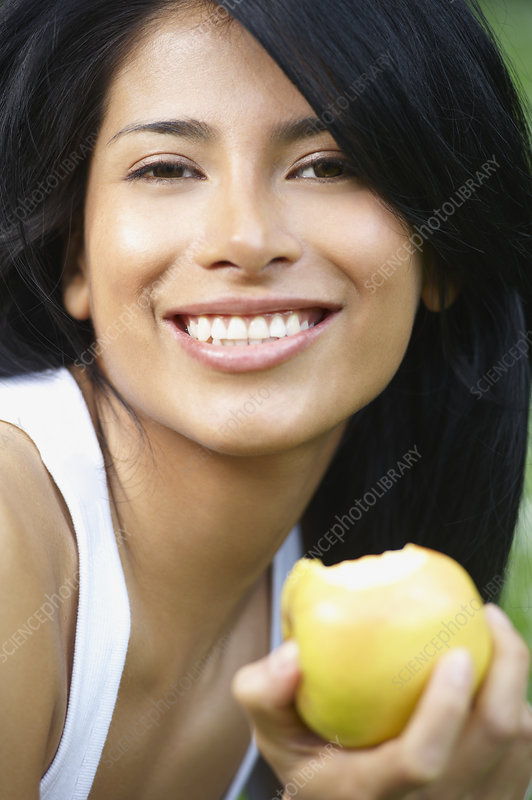 Woman eating an apple, smiling