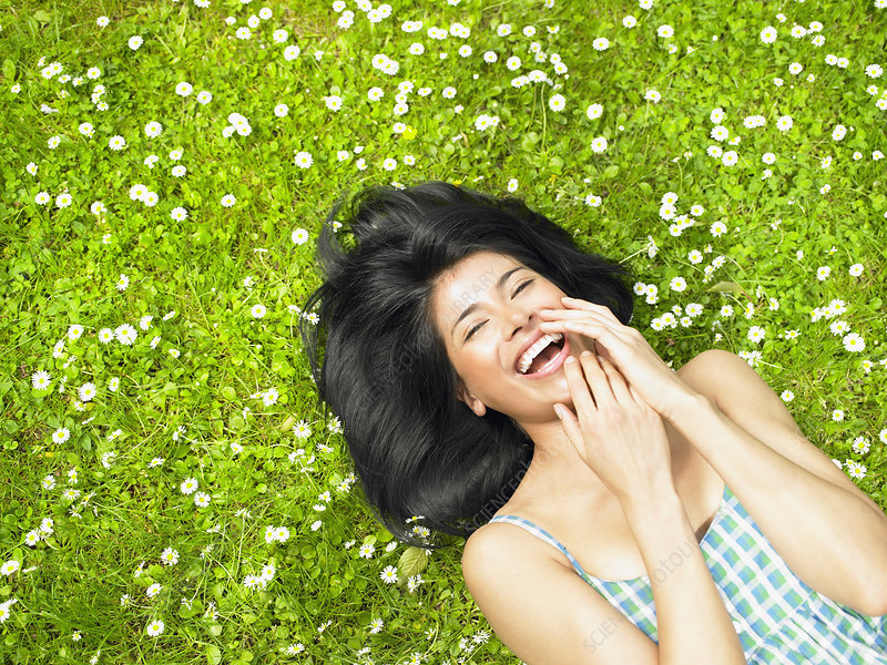 Woman smiling, surrounded by daisies