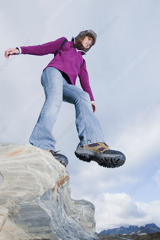 Young Woman Leaping Off Rocks