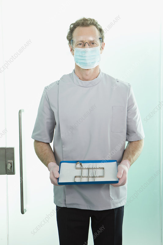 A dentist holding his tools