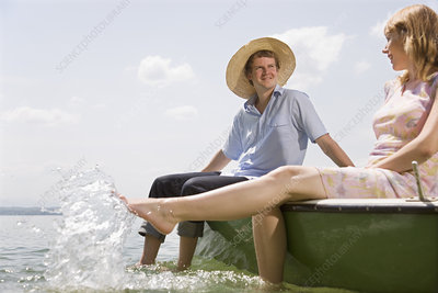 woman and man in rowing boat on lake