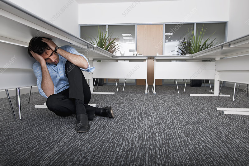 man hiding under desk