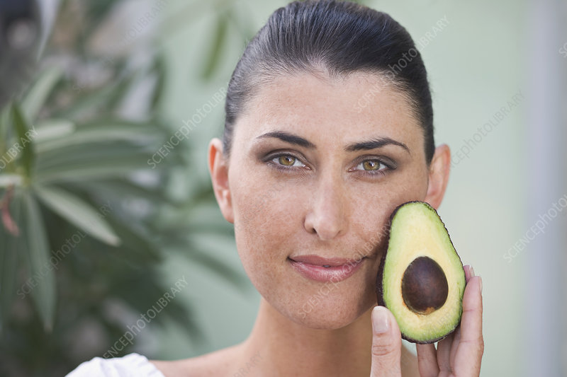 A female beauty holding an avocado