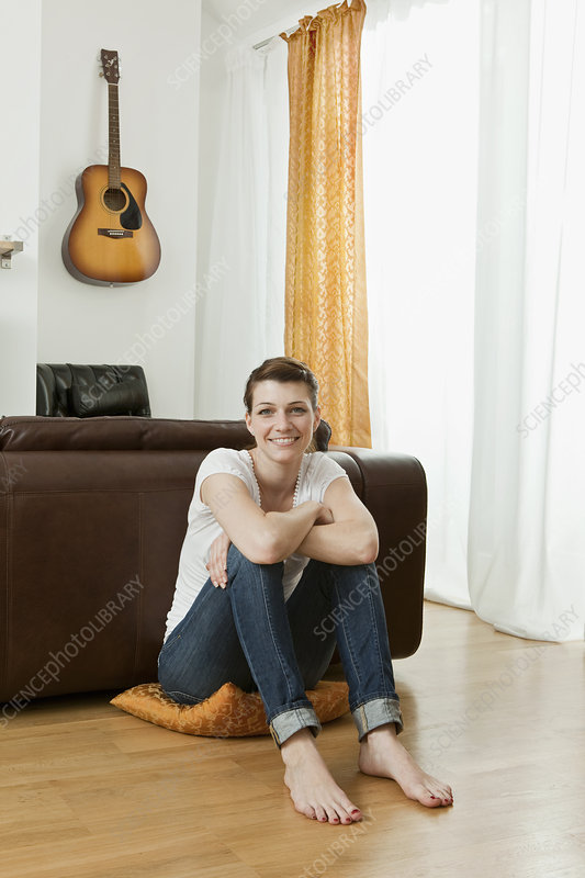 Young woman sitting on living room floor