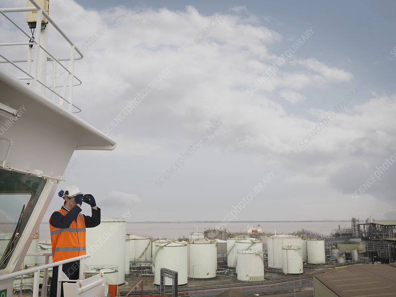 Port Worker With Binoculars On Ship