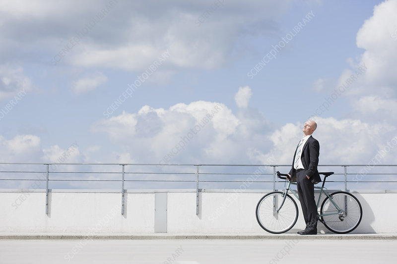 man with bycicle on car park