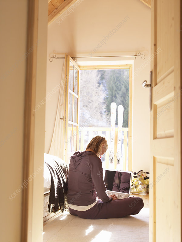 woman on laptop in bedroom of chalet