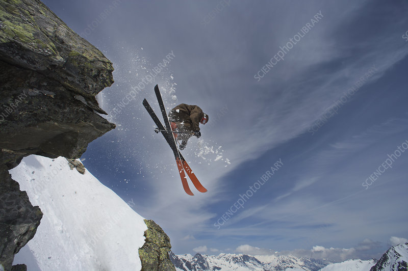 Skier jumping off a rock