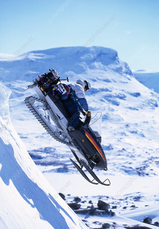 Snowboarder jumping on a skidoo