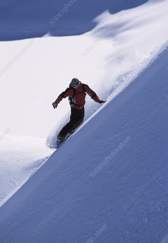 Snowboarder turning a slope